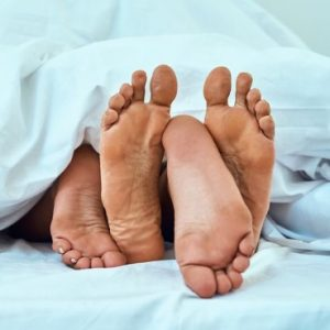 the feet of a couple between the bed sheets