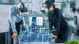 Male and Female Architects Wearing Augmented Reality Headsets Work with 3D City Model.